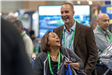 Two delegates laughing during a visit to the 2018 League Conference Exhibit floor.