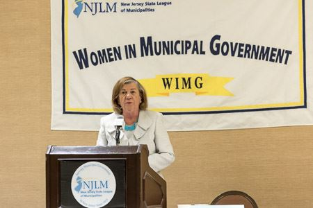 Speaker in Front of Women in Municipal Government Banner