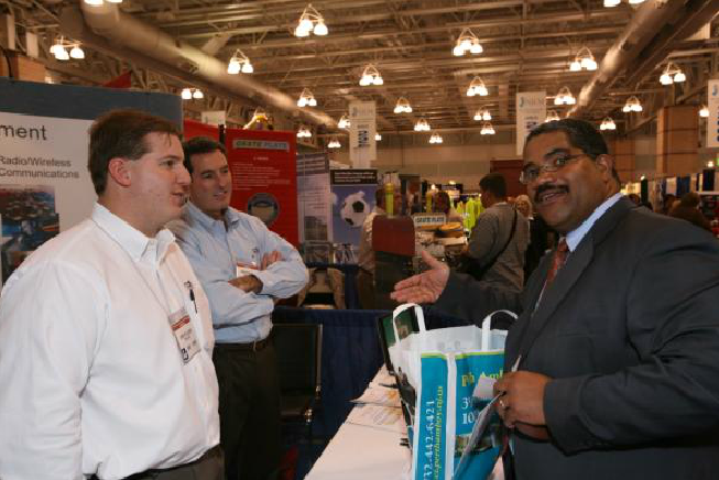 Man Gesturing to Booth Attendees