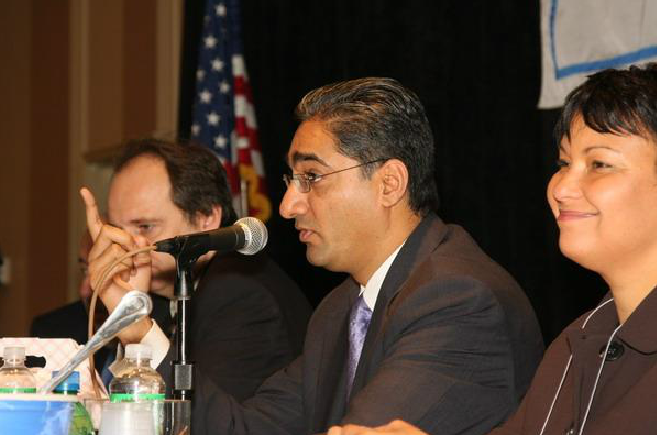 Man Speaking into Microphone and Pointing