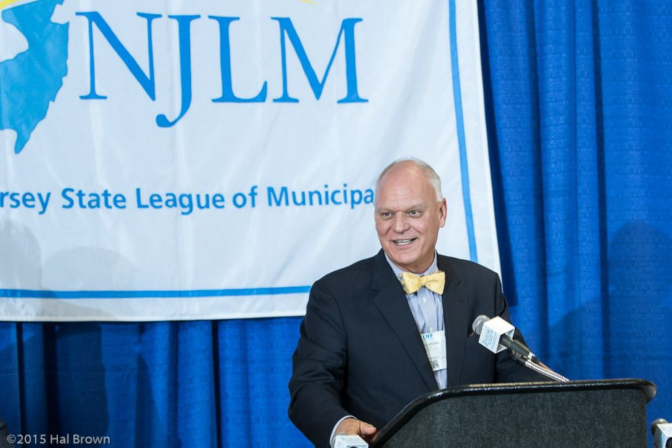 Man Standing Behind Podium In Front of NJLM Banner