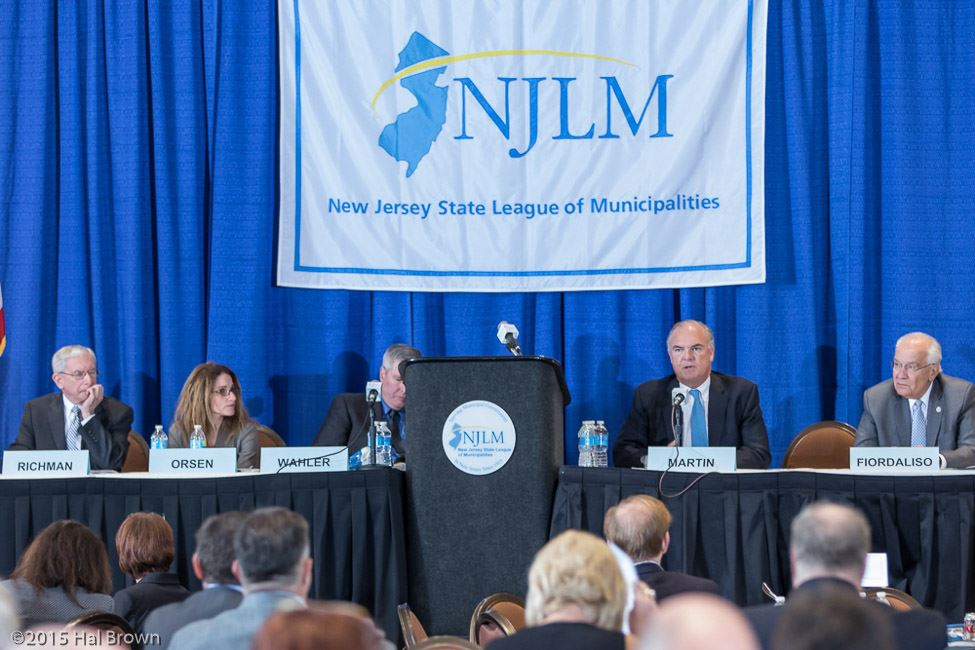 Panelists at a Long Table With NJLM Banner Behind