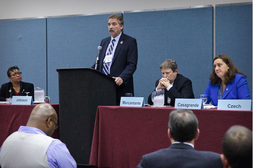 Man Speaks at Podium With Other Panelists Sitting at His Either Side