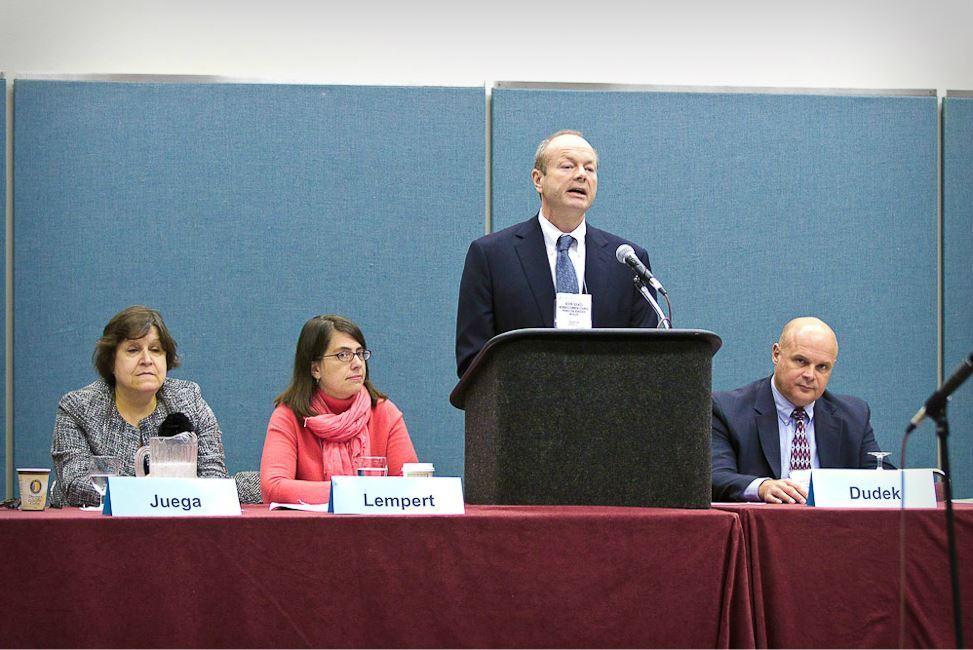 Man Speaks at Podium With Panelists Juega, Lempert, and Dudek Sitting on His Either Side
