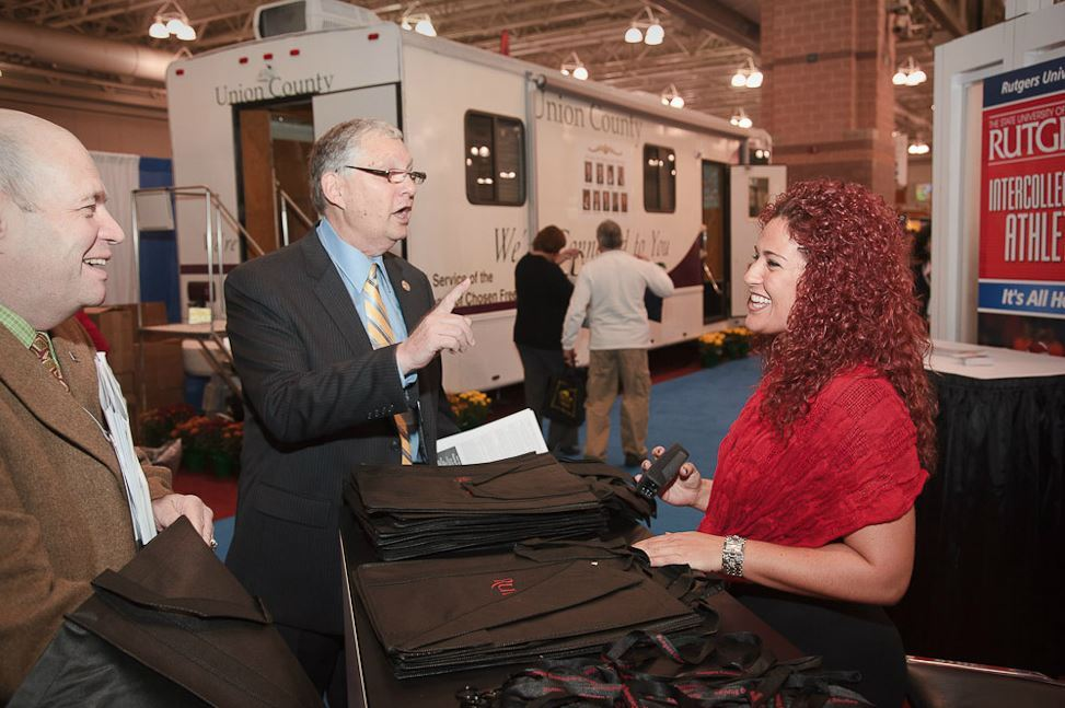 Men Speak to Woman at Exhibitor Booth