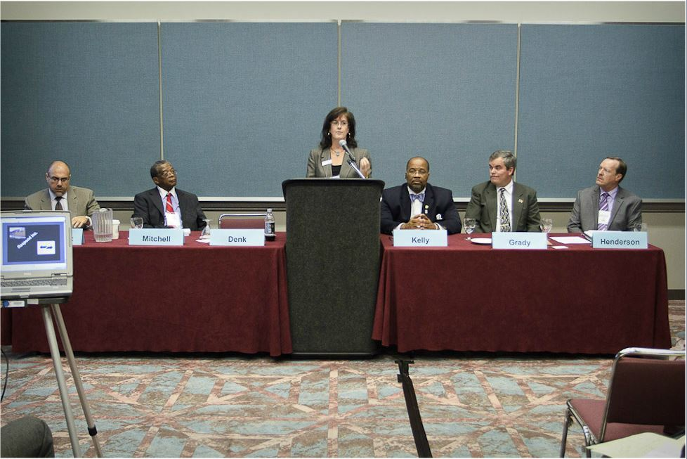 Panelist Denk Speaks at Podium While Other Panelists Sit at Either of Her Sides