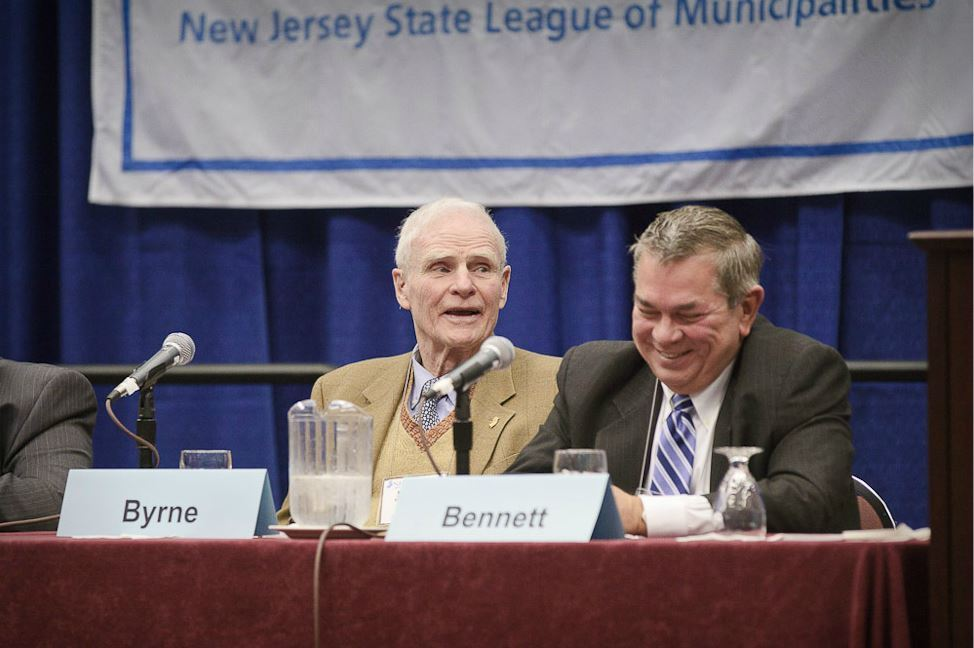 Panelists Byrne and Bennet Smile Together at Panel Table