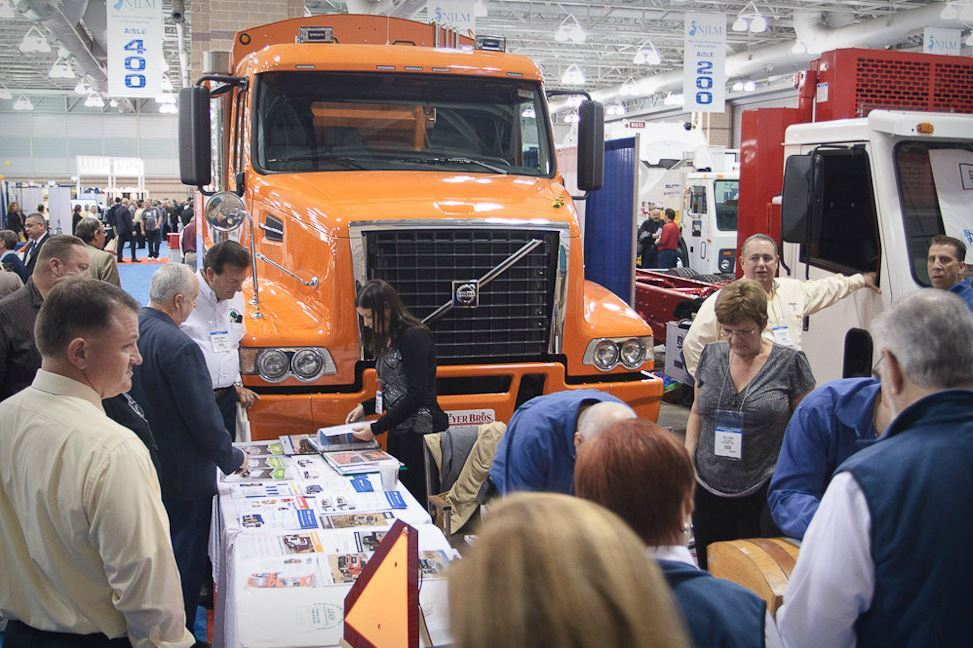 People Stand at Exhibitor Booth Next to Municipal Vehicles