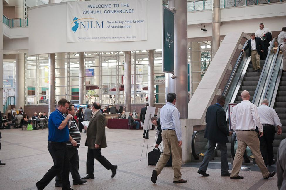 People Walk Toward Escalator in Convention Center