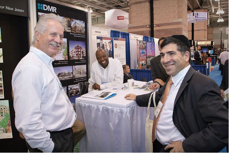 Three Men Stand at DMR Exhibit Booth