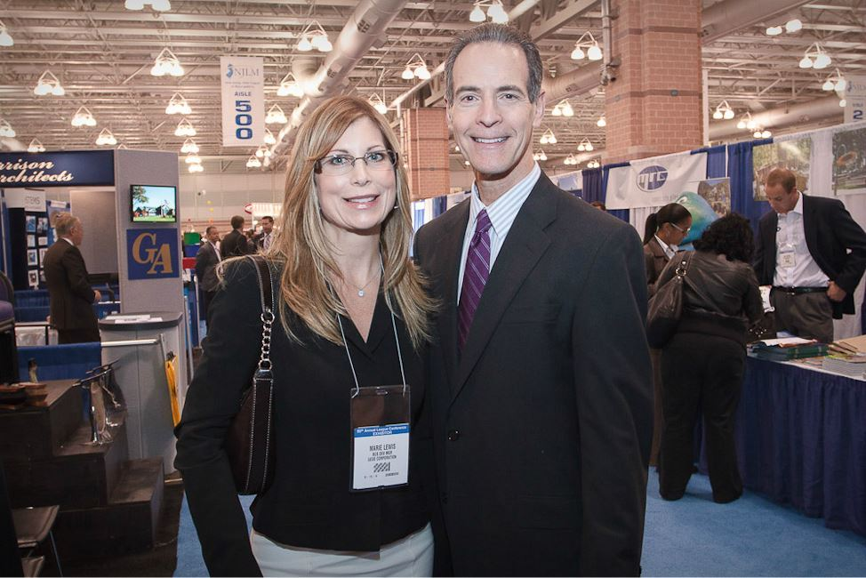 Woman and Man Smile for Photo on Exhibit Floor