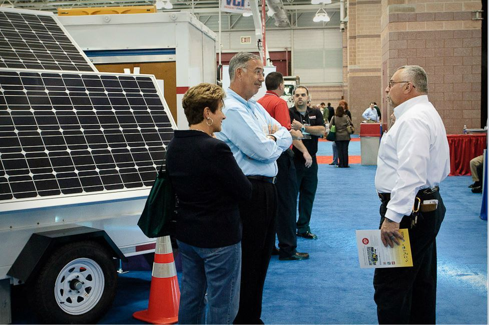 Woman and Man Speak to Another Man With Solar Panels on Vehicle Behind Them