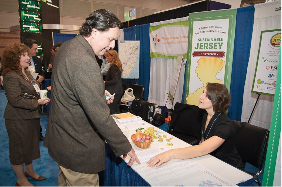 Woman at Sustainable Jersey Booth Speaks to Man
