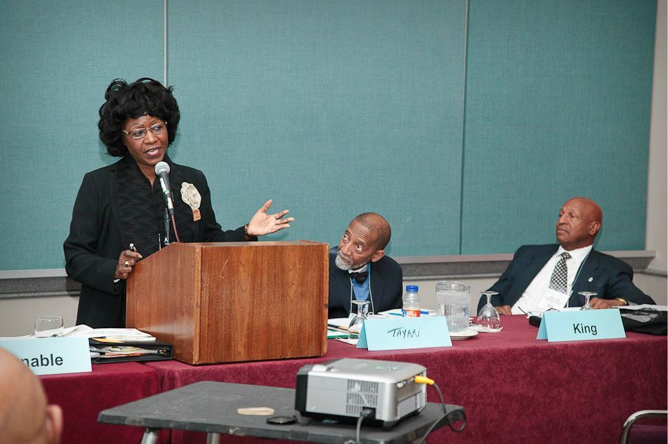 Woman Speaks at Podium as Panelists Tayari and King Watch From Her Left