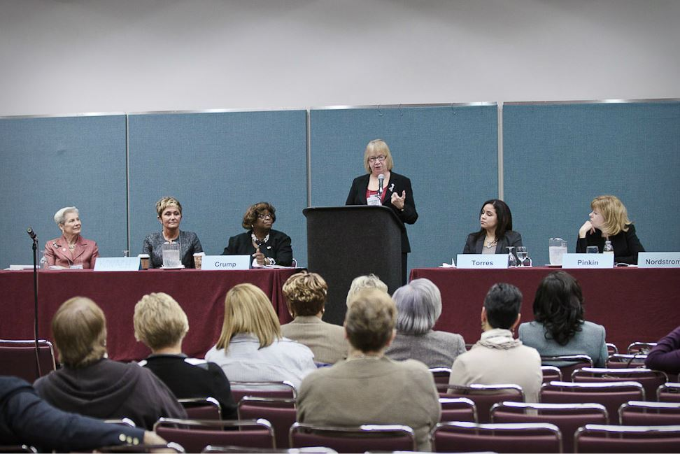 Woman Speaks at Podium While Other Female Panelists Sit at Her Either Side