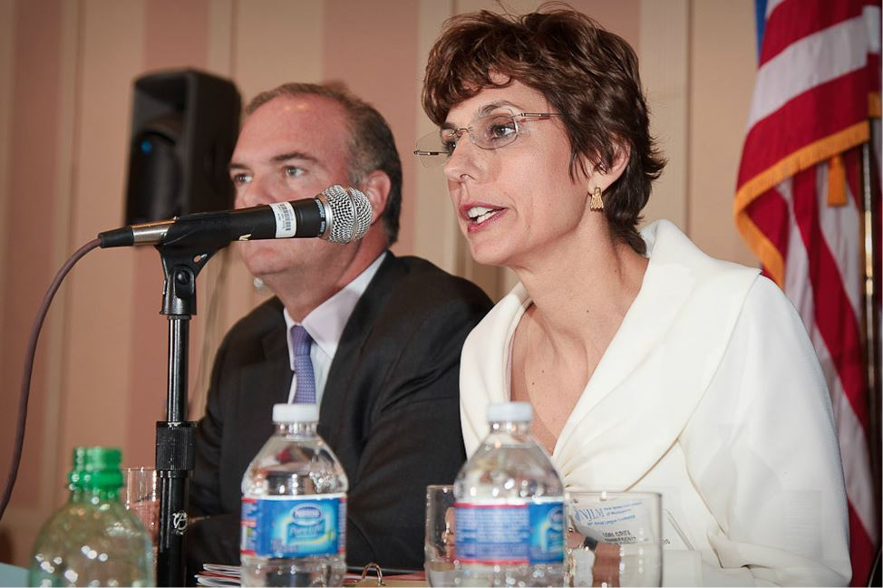 Woman Speaks Into Microphone at Panelist Table