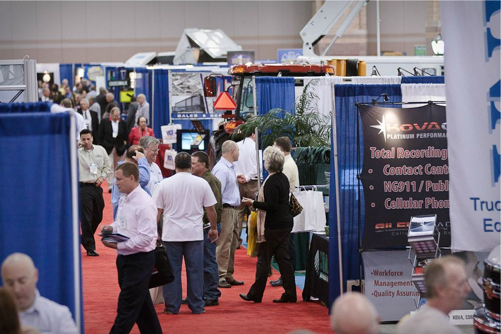 Conference Goers Walk Down Aisle on Exhibitor Booth Floor