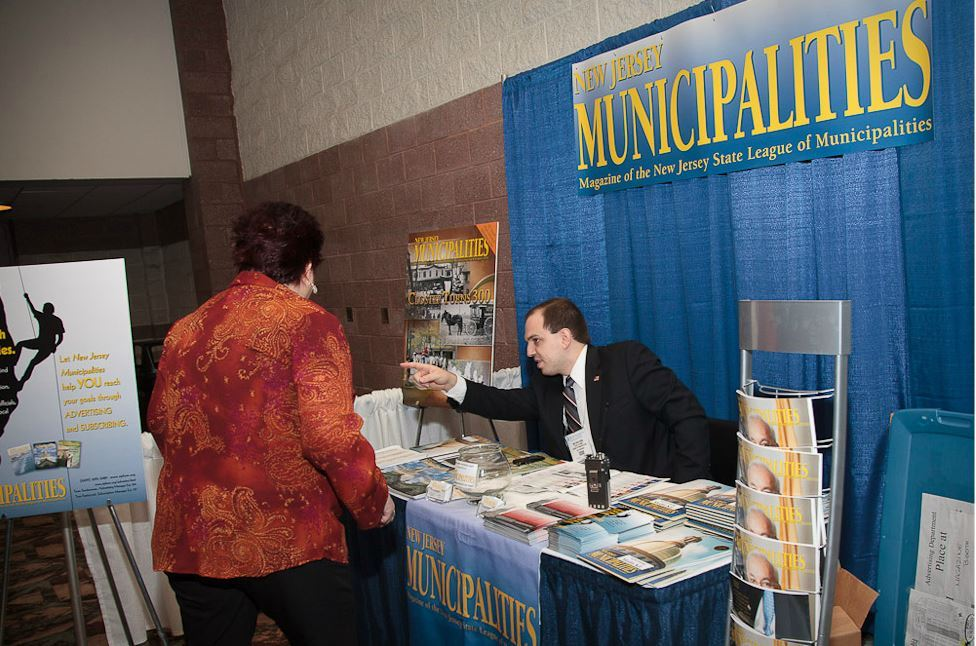 Man at New Jersey Municipalities Booth Points at Something for Woman