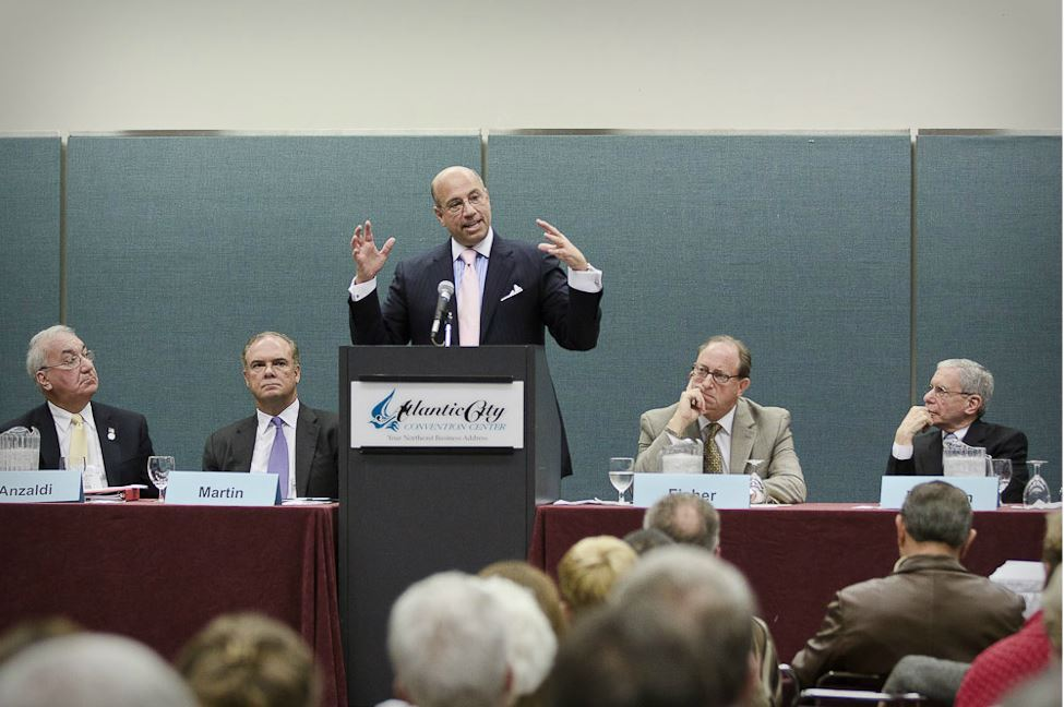 Man Speaks at Podium as Other Panelists and Audience Listen