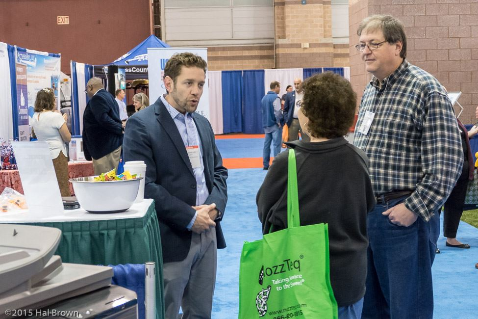 Exhibitor Speaks to Man and Woman