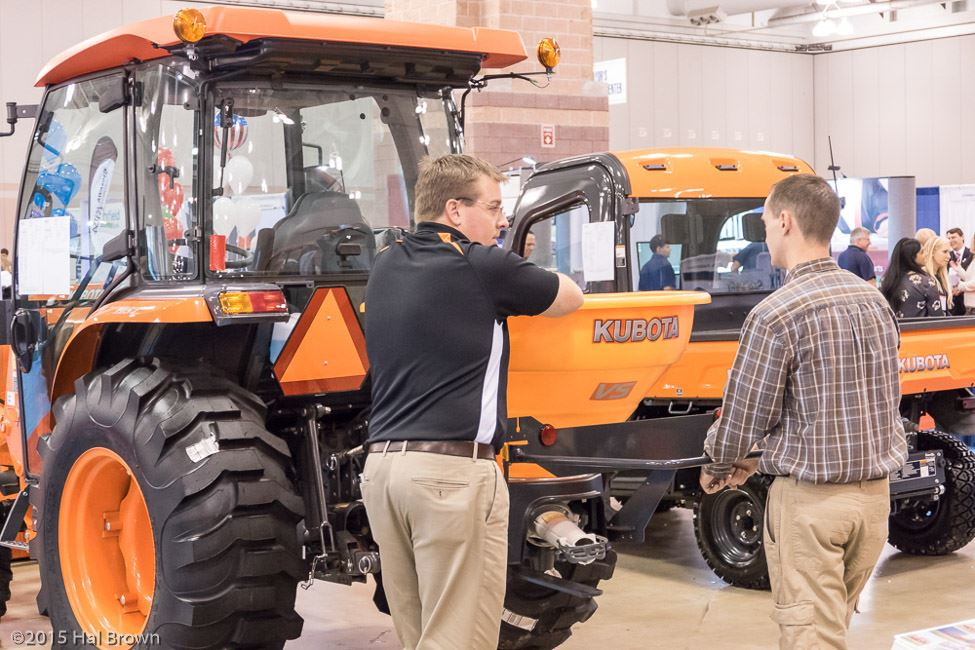 Men Talking by Orange Tractor and Equipment
