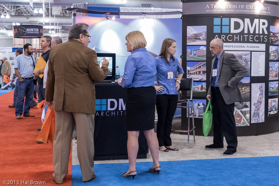 People Conversing in Front of DMR Architects Booth