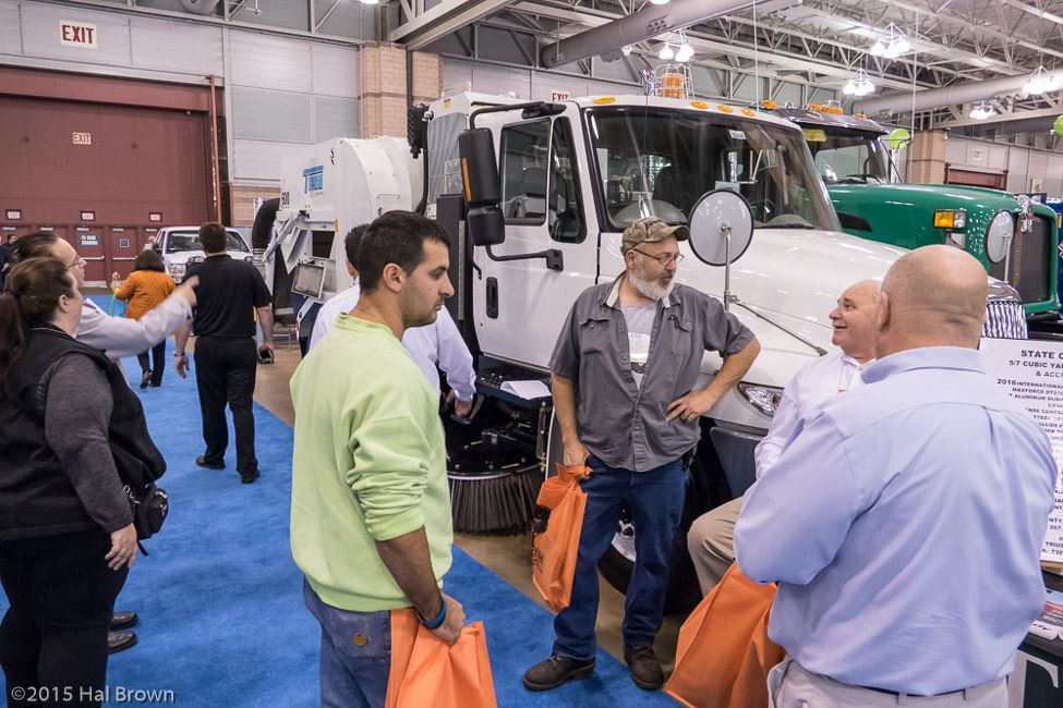 People Having a Discussion in Front of Large White Display Truck